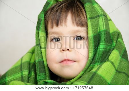 Kid portrait in blanket warming happy smiling kid face expressing emotion little girl looking at camera warm blanketcomfortable winter concept