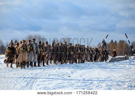 Column of the Red army infantry walks on winter sunny road. Reconstruction of the winter defensive battles of the Red Army in WWII (1944 year).