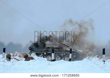 Winter view of the burning german tank (panzer) in the battle. Reconstruction of the winter defensive battles of the Red Army in WWII (1944 year).