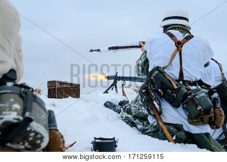 Wehrmacht machine-gun crew in action. Reconstruction of the winter defensive battles of the Red Army in WWII (1944 year).