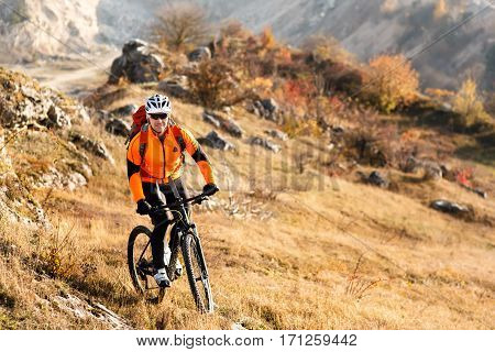 Cyclist in Red Jacket Riding the Bike Rocky Hill. Extreme Sport Concept. Space for Text. Cycler in the helmet and glasses with red backpack. Travel in the countryside. Spring season.