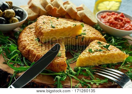 Spanish classic tortilla with potatoes, olives, tomatoes, rucola, bread and herbs