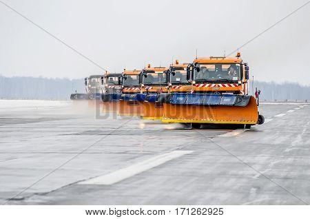Snow machines on the asphalt runway rain snow removal. Russia, Tyumen city, Airport Roschino 13 March 2014