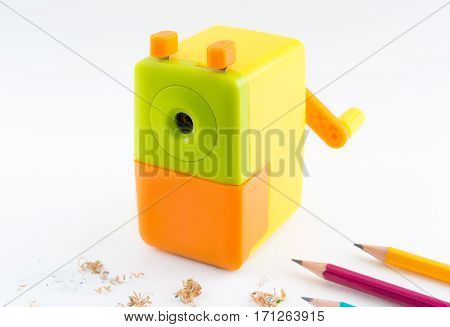 colorful rotary pencil sharpener with pencil on white background