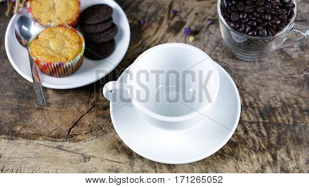 Coffee cup and chocolate cookies on a wood table with dark roasting coffee beans.