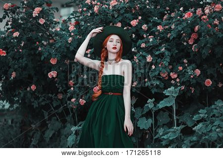 The red-haired girl in a long dress and vintage green hat posing against a background of peach roses. Romantic lady with a red plait and red lips in the style of the Enlightenment. Flower garden