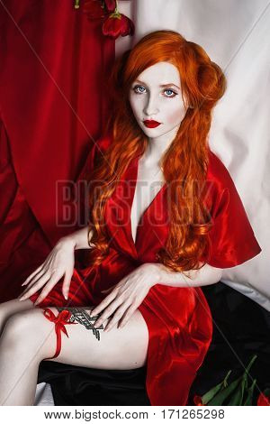 The red-haired doll girl in pin-up style with long hair posing in sexy scarlet robe on purple - white background. Young red-haired woman with a garter on her leg. Model in retro style
