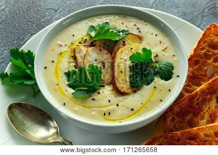 Creamy chicken soup with vegetables in bowl with chiabatta toast, parsley and nigela seeds sprinkle.