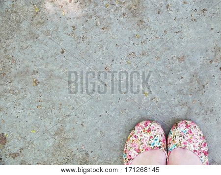 Feemale feet in woman shoes. Feet on asphalt, top view