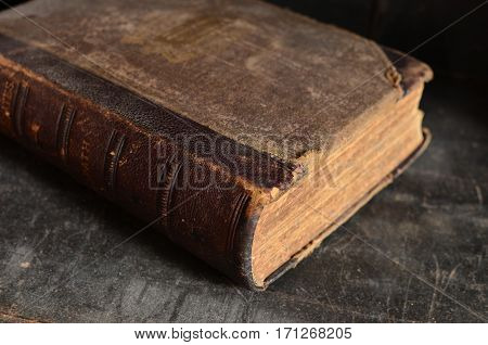 Old leather bound book laying on a dusty wooden bookshelf