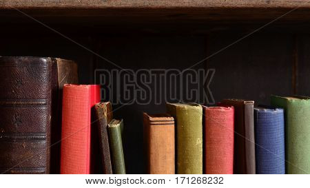 Row of colorful vintage books on an old wooden bookshelf