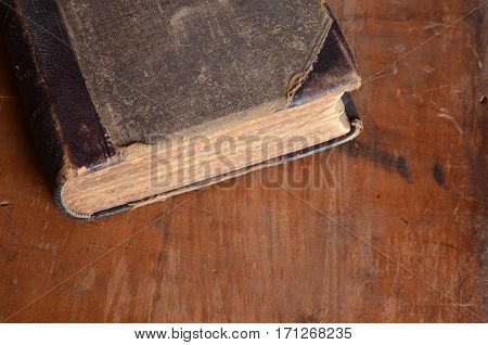 Antique leather bound book laying on an old rustic wood