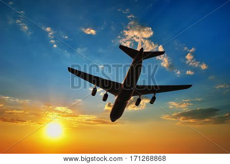 Airplane silhouette in sunset sky. Airplane travel