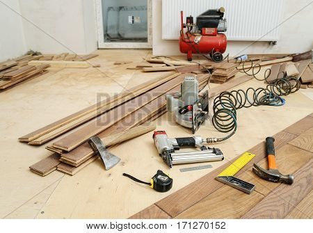 Installing a wooden floor. Carpenter's tools on the floor.