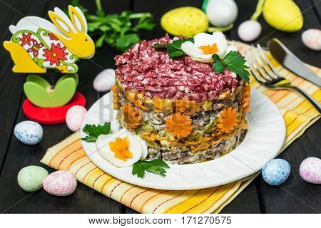 Multilayer festive salad with beef pickled cucumbers and carrots on a blue wooden table with eggs and bunny. Easter food Easter recipe. Selective focus