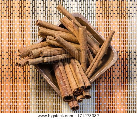 Oriental fragrant cinnamon sticks in wooden bowl