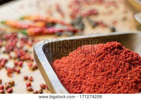 Fragrance paprika in wooden bowl on pepper background