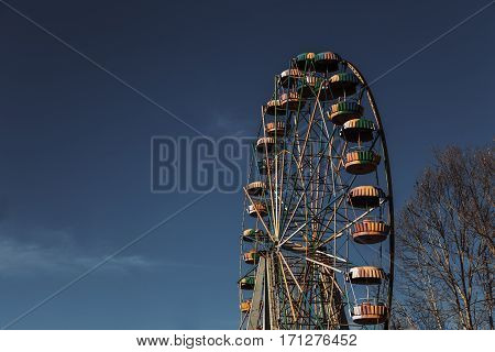 Abandoned ferris wheel against a blue sky.