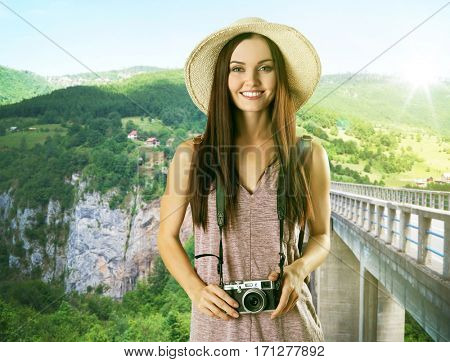 Young woman with camera on beautiful landscape background