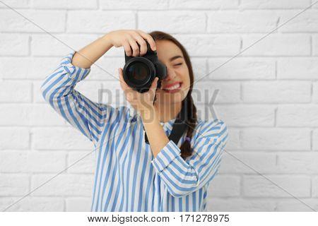 Beautiful young photographer near light brick wall