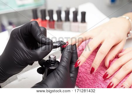 Woman having a manicure in a beauty salon with the beautician filing her nails with a file