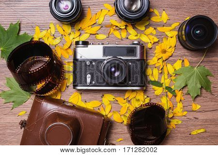 Professional attributes for photographing. Lenses and vintage camera and film on wooden background. Shooting flower arrangement and retro technology. Green leaves. Cover for an old camera.