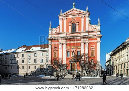 LJUBLJANA, SLOVENIA - JANUARY 19, 2107: The Franciscan Church of the Annunciation built between 1646 and 1660 in Baroque style. Its red colour is symbolic of the Franciscan monastic order.