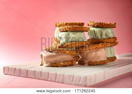Delicious kiwi and chocolate ice cream cookie sandwiches on white wooden board and pink background