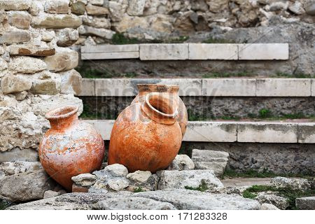 Antique ceramic pots. Old clay vases outdoors. Archaeological still life. Selective focus.