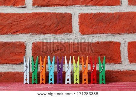 Plastic Clothespins On A Brick Wall Background