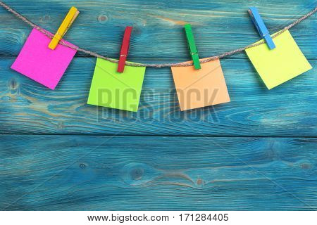 Clothespin hanging with colored blank photo papers on wooden background texture