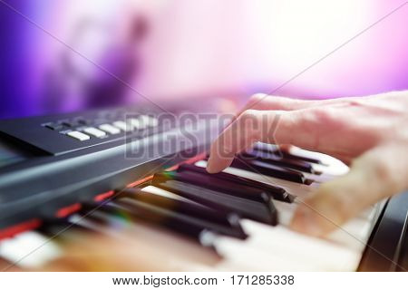Pianist musician performing live playing keyboard in a band with saxophone player in background