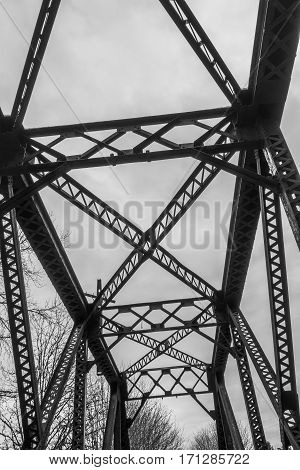 A view of a silhouette of a bridge trestle that spans the Cedar River in Renton Washington. Black and white image.