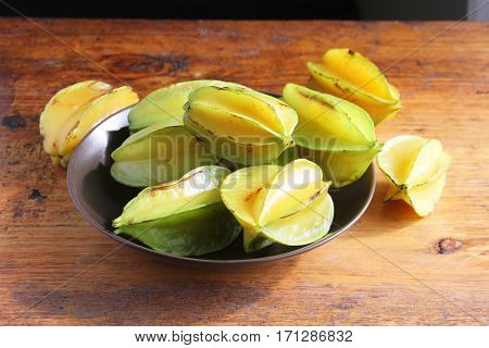 Bowl of whole star fruit or carambola on antique wooden table in Peru