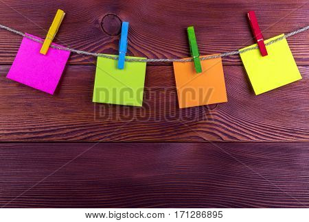 Clothespin hanging with blank photo papers on wooden background texture