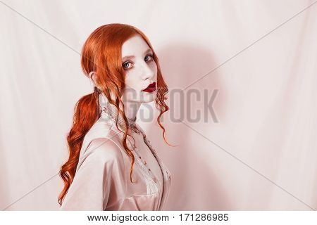 Sexy red-haired girl with the hair gathered in a ponytail holding a lilac flower in the hands. Gothic tattoo model in erotic underwear with a slender waist. The vampire in pastel colors.