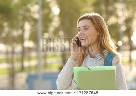 Happy student girl walking and calling on mobile phone outdoors with a green background