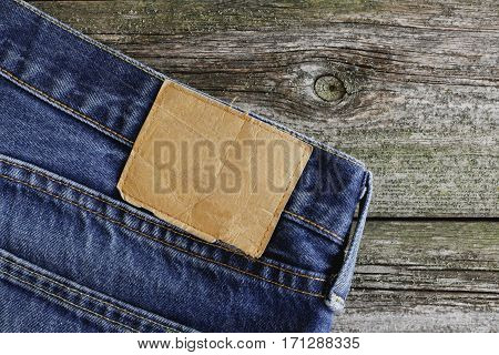 Blank leather label back view of jeans old wooden table, closeup,