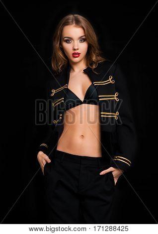 Beautiful fashion model wearing black jacket with golden stripes luxury fancy clothing on black background