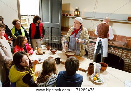 LONDON - CIRCA 2014: Chefs in traditional dress demonstrate cookery at the Royal Kitchens Kew Gardens London UK