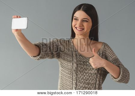 Attractive young woman in casual clothes is doing selfie using a smart phone showing Ok sign and smiling on gray background