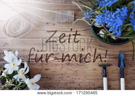 German Text Zeit Fuer Mich Means Time For Me. Sunny Spring Flowers Like Grape Hyacinth And Crocus. Gardening Tools Like Rake And Shovel. Hemp Fabric Ribbon. Aged Wooden Background
