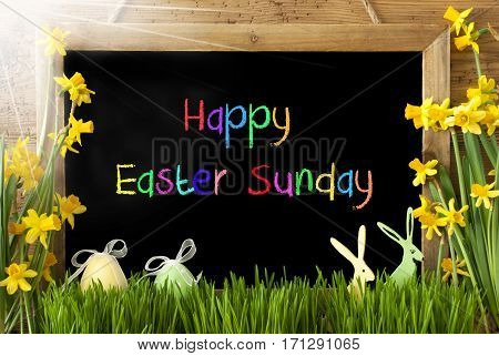 Blackboard With Colorful English Text Happy Easter Sunday. Sunny Spring Flowers Nacissus Or Daffodil With Grass, Easter Egg And Bunny. Rustic Aged Wooden Background.