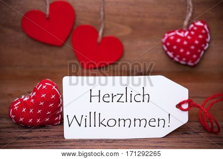 Label With German Text Herzlich Willkommen Means Welcome. White Label With Red Textile Hearts. Retro Brown Wooden Background.