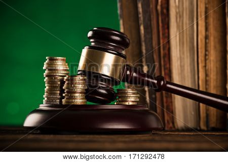 brown gavel with a brass band on wooden table.
