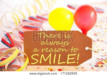 One Label With English Text Quote There Is Always A Reason To Smile. Party Decoration Like Streamer, Confetti And Balloons. Wooden Background With Vintage, Retro Or Rustic Syle
