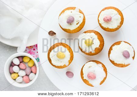 Easter birds nest cupcakes with chocolate candy eggs whipped cream and cotton candy recipe step by step