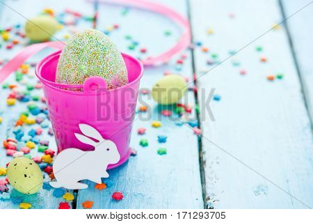 Colorful Easter background with decorative Easter egg Easter bunny and sugar sprinkling