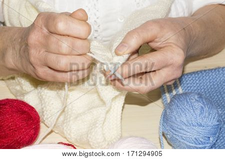 Detail of the hands of a person sewing with woolen thread