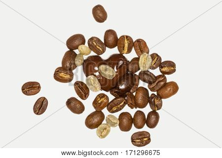 Close Up Of One Pieces Of Dark Chocolate And Coffee Beans On A White Background